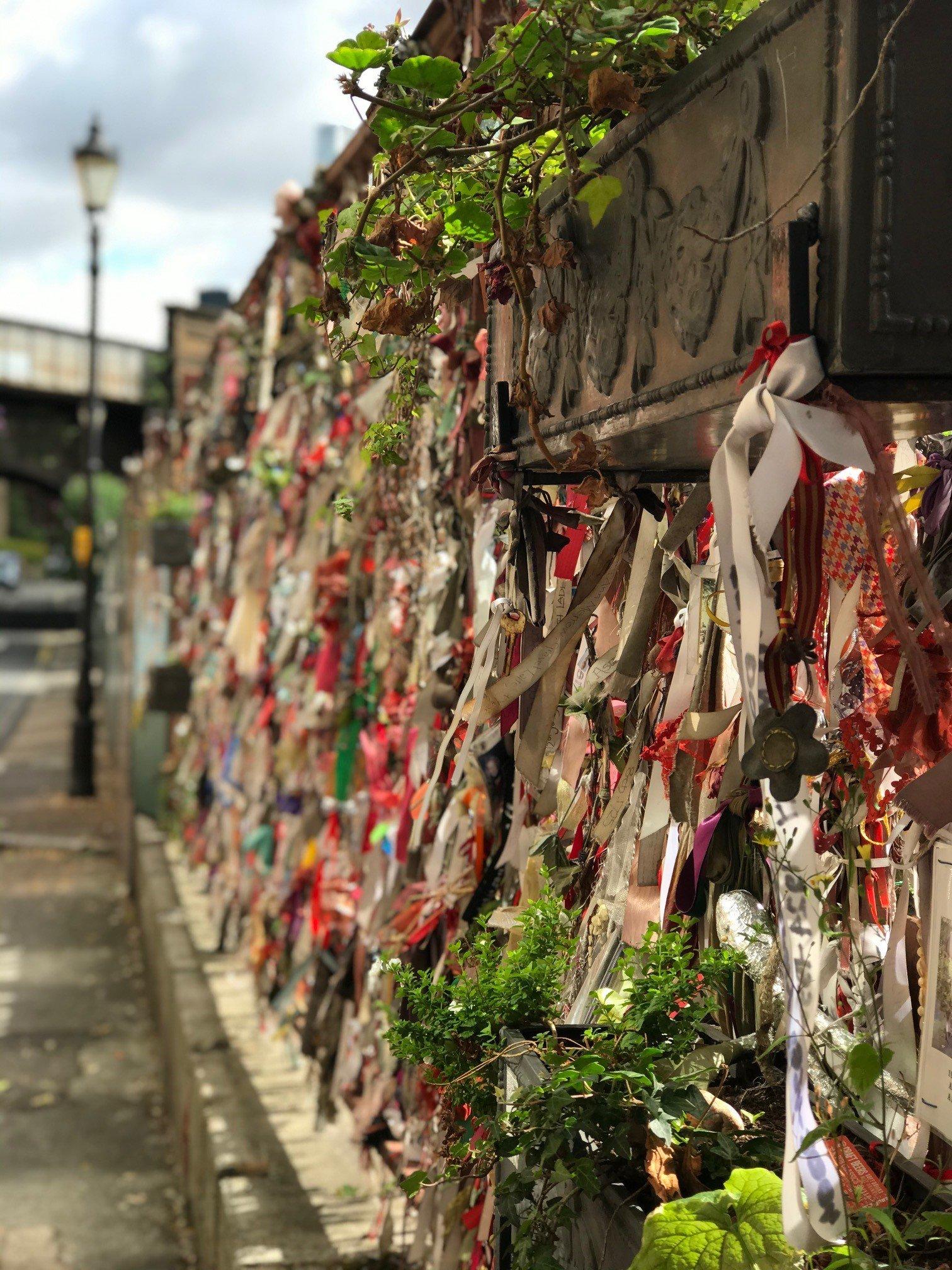 Tied ribbon memorial wall at Crossbones Graveyard gates in Redcross Way